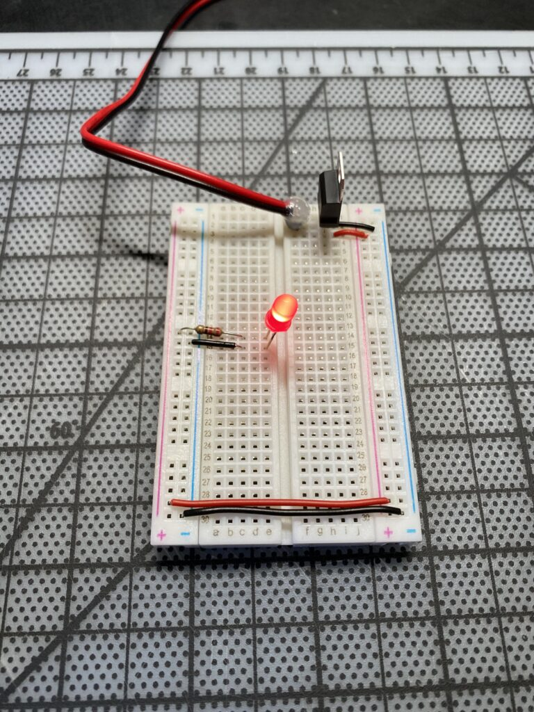 Red LED lit on a breadboard