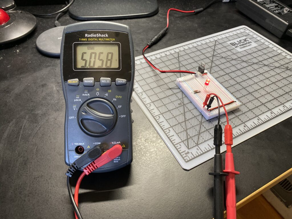 Multimeter probes reading 5.058 volts on a circuit board with red LED