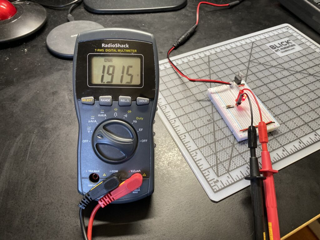 Probing the voltage drop across the red LED reads 1.915 volts.