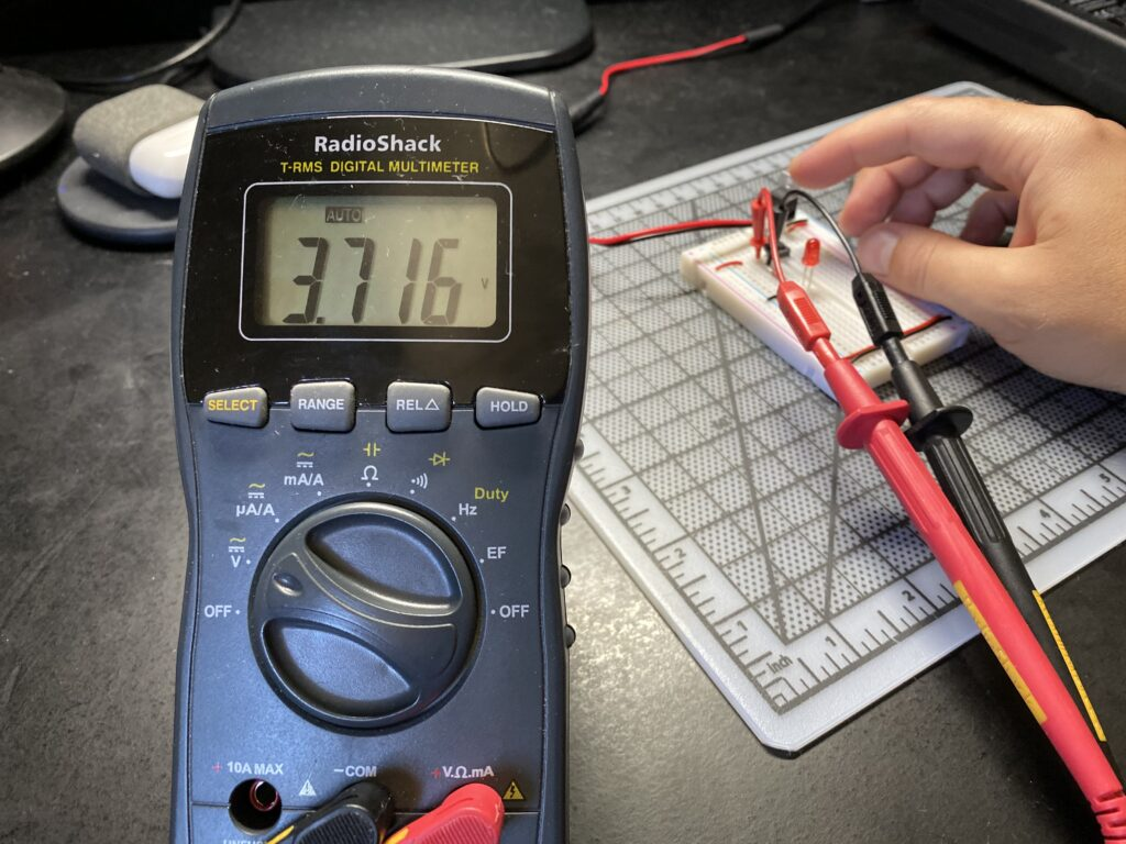 Multimeter reading 3.716 volts across a pushbutton on a breadboard