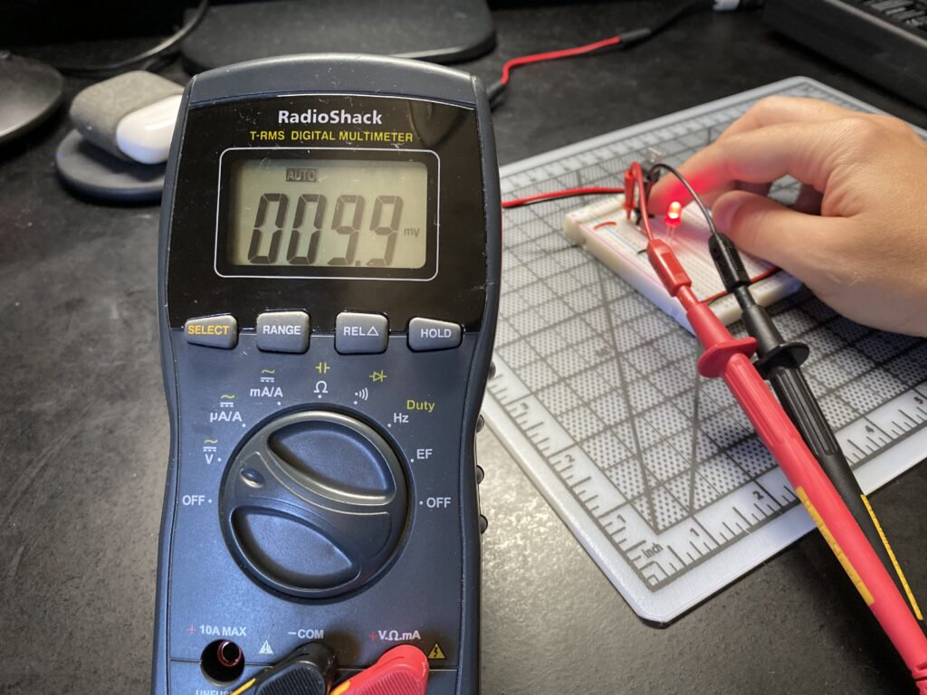 Multimeter reading 9.9 millivolts across a push button on a breadboard