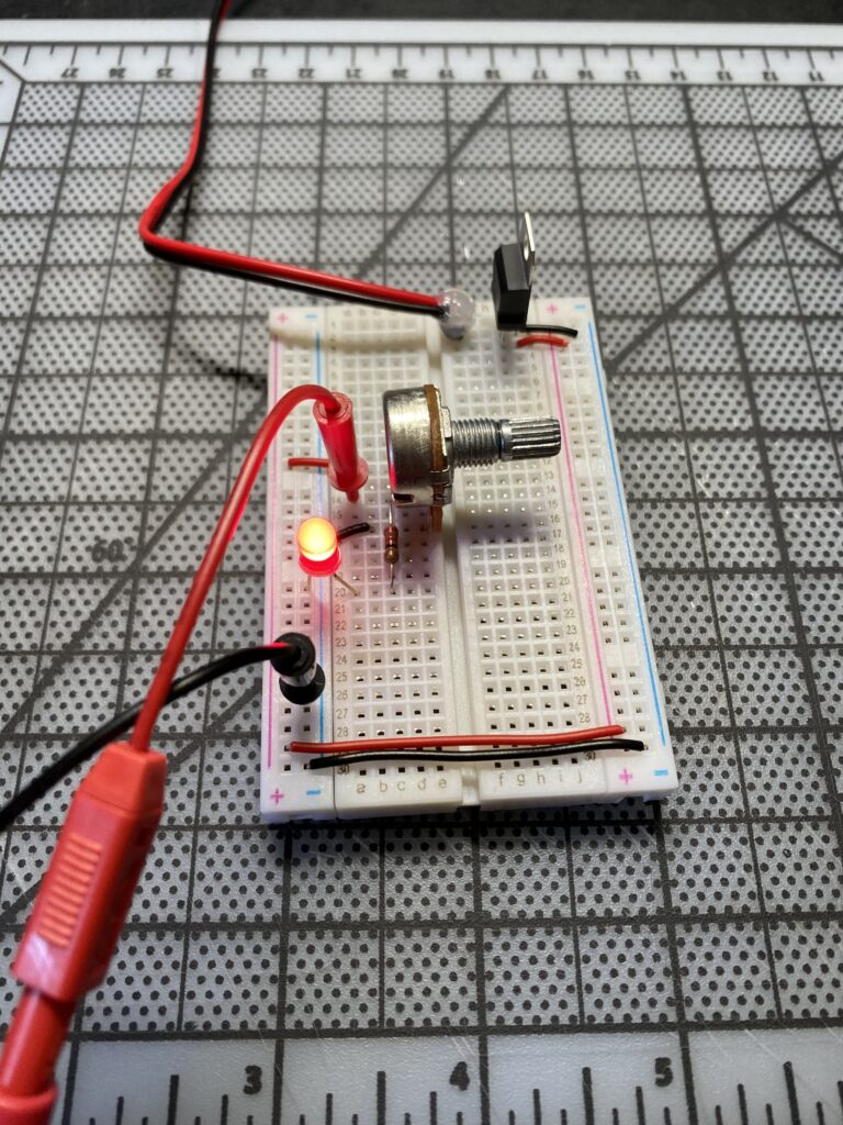 Circuit on a breadboard with red lit LED